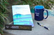 """A textbook titled """"Listing, Assessment, and Taxation of Property in North Carolina"""" and a bookmark branded with the Zacchaeus Legal Services logo sit next to greenery, a black ink pen, and a UNC School of Government mug."""