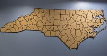 A mounted corkboard map in the shape of North Carolina hangs on a blue wall